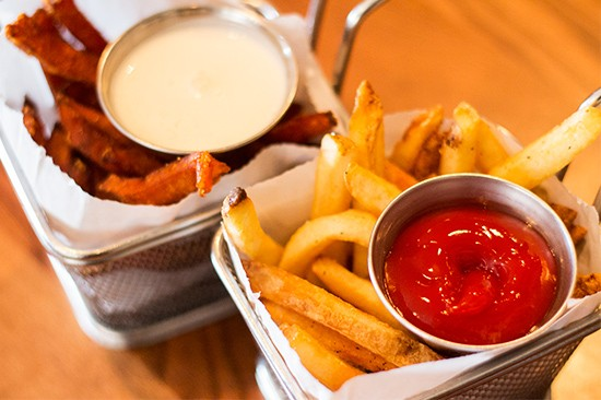 Sides of fries and sweet potato fries.