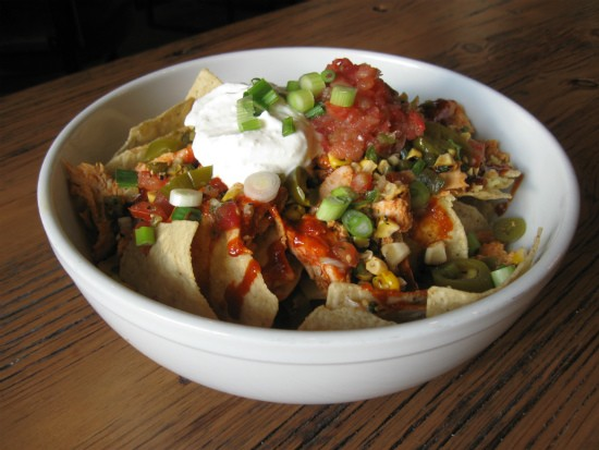 Nachos with cheddar cheese, jalapenos, poblano pico, smoked-tomato chutney and sour cream at the Fifth Wheel. - ALICE TELIOS