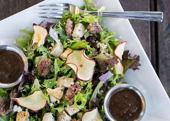 "The ""Apple Orchard"" salad brings garden greens and arcadian lettuce dressed with roasted chicken, red onions, apple chips, gorgonzola cheese, sweet pecans and balsamic vinaigrette.. 