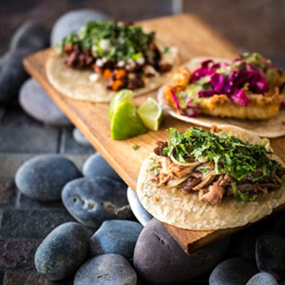 Asada taco (beef brisket with seared onion & salsa), Pescado taco (tempura style fish with a vinaigrette coleslaw and salsa verde), and Al Pastor taco (pulled pork, seared pineapple, Guajillo and Ancho chiles). | Jennifer Silverberg