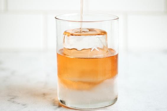 A drink being poured over the ice cylinder at Taste - JENNIFER SILVERBERG