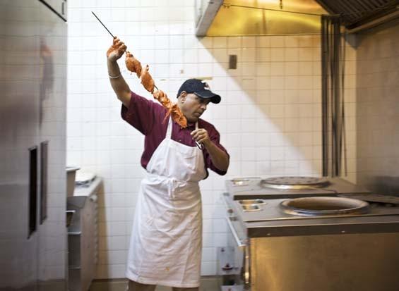 Tandoor chef Inderjeet Grewal puts skewered chicken into the tandoor oven. See full slideshow here. - PHOTO: JENNIFER SILVERBERG