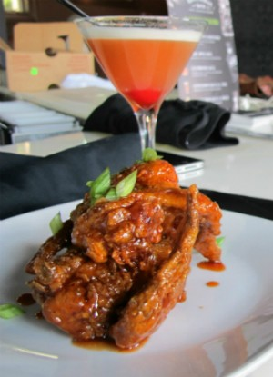 """The chicken wings with a """"Pineapple Upside Down"""" cocktail at Soho. - REASE KIRCHNER"""