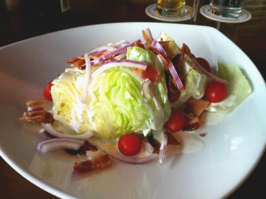 The wedge salad at the Shaved Duck, piled high with iceberg lettuce, crispy bacon, cherry tomatoes and shaved red onion bathed in tangy ranch dressing. - LIZ MILLER