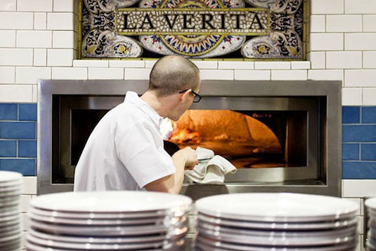 Brian Moxey slides a pizza into Pastaria's wood-fired oven. | Jennifer Silverberg