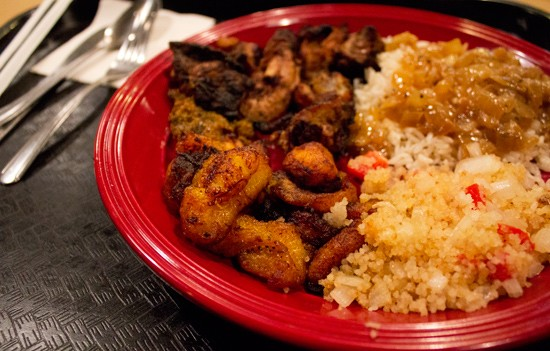 Alloco (fried plantain) and attieke (seasoned couscous-like cassava mixed with tomato, onion and hot pepper) on a jerk chicken plate. - MABEL SUEN