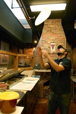 Former culinary manager Dylan Watson tosses a pizza. - ETTIE BERNEKING