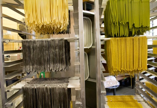Fresh noodles including flavors like regular egg, squid ink, spinach and lemon pepper hang on rods after being run through a cutter. - MABEL SUEN