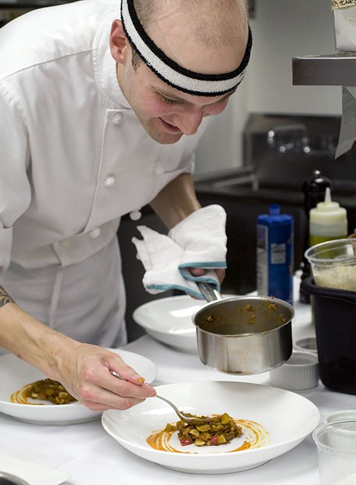Sous/pastry chef Sean Harmon plating the wild striped bass. See more photos from the kitchen at Fond. - PHOTO: JENNIFER SILVERBERG
