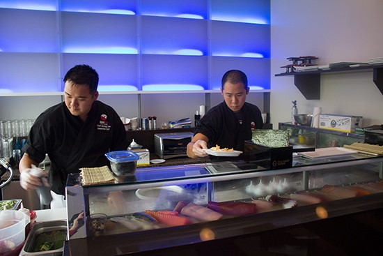 Chef Soung Lee prepares dishes at the sushi bar with another chef.