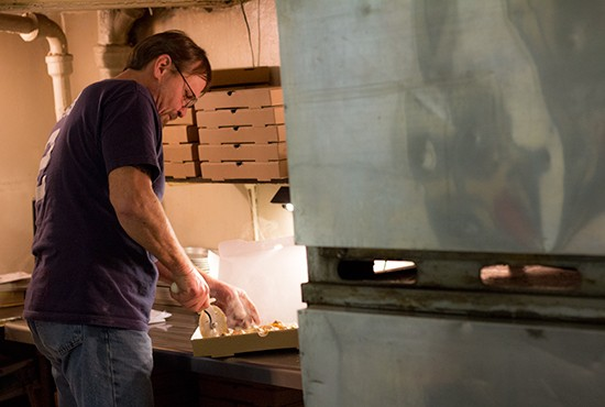 General manager Tom Nix slices up a steaming-hot pizza in the kitchen.