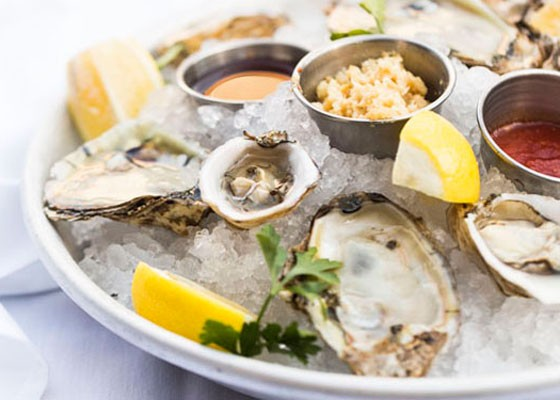 Bluepoint and Kusshi Oysters served with red champagne mignonette, cocktail sauce and fresh horseradish. | Jennifer Silverberg