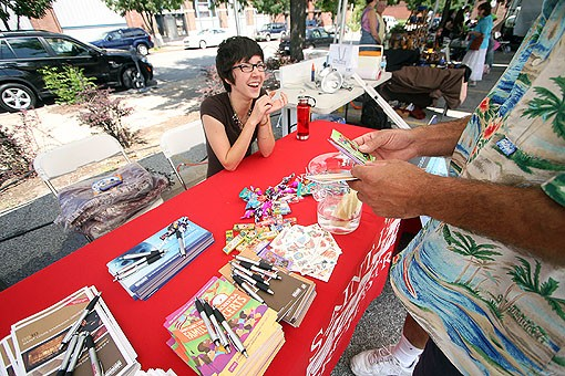 Sarah Christiansan offers a man some extra goodies at the St. Louis Symphony Orchestra booth. See more photos from The Lot here. - PHOTO: NICK SCHNELLE