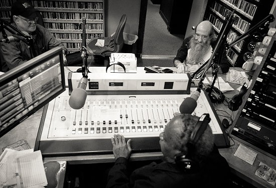 Gabriel (bottom) sits at the control desk in KDHX's main studio with Dennis Brannaker (right) and Hound Dog Brown (left) - BRIAN HEFFERNAN