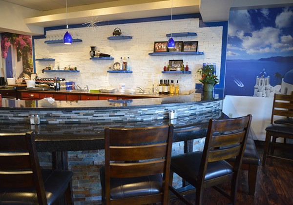 The semi-circle bar at Greek Kitchen is bookended by images of Greek landscapes. - TOM HELLAUER
