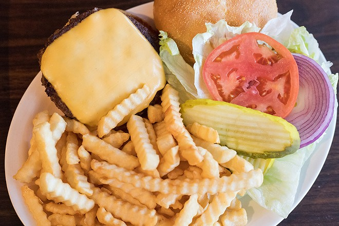 The cheeseburger is topped with American cheese, lettuce, tomato, onions and pickles. - MABEL SUEN