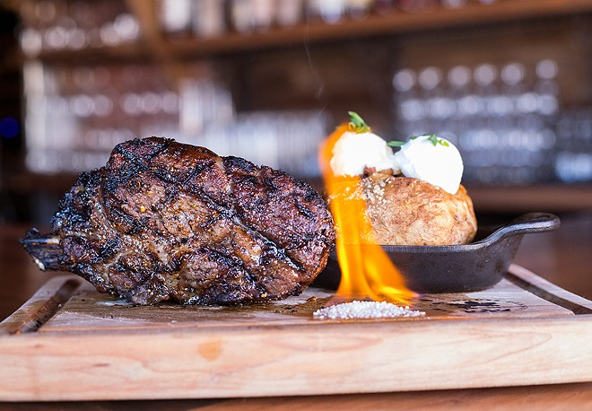 Superior steaks include a 22-ounce bone-in ribeye, shown here with a loaded baked potato. - MABEL SUEN