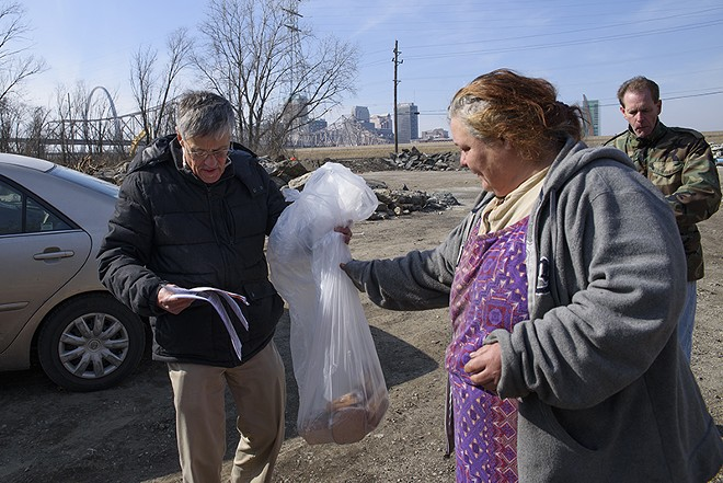 Ray Redlich (in black) and Chris Ohnimus, pictured here giving sandwiches to a resident of a homeless camp, were ticketed for distributing sandwiches in St. Louis. - NICK SCHNELLE