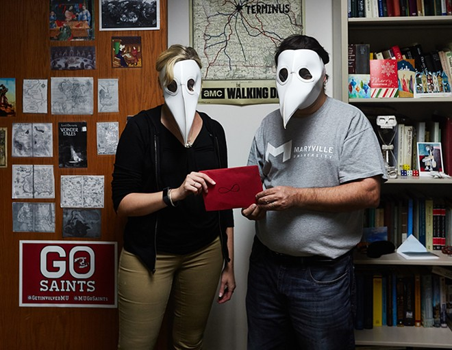 "Donning ""plague doctor"" masks, professors Kyra Krakos and John Marino hold an envelope that will change the fates of their eighteen students. - THEO WELLING"