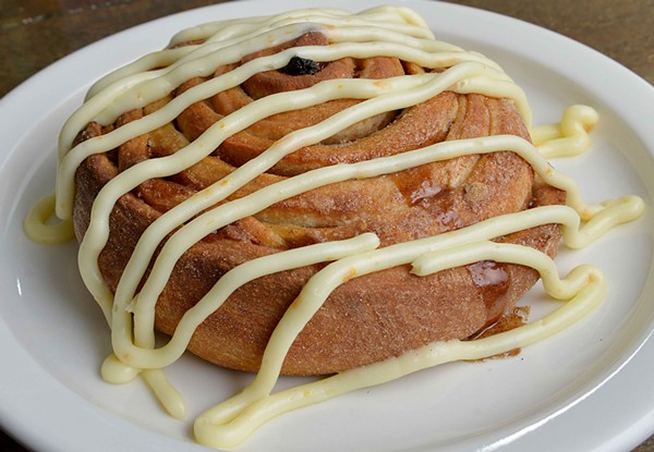 """The """"XL Cinnamon Roll"""" has raisins and pecans baked inside. On top is orange cream cheese icing. - TOM HELLAUER"""