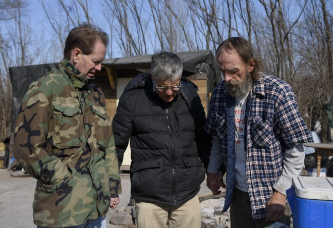 From left, Chris Ohnimus and Ray Redlich pray with Robert Gibson at homeless encampment in 2018 in East St. Louis. - NICK SCHNELLE