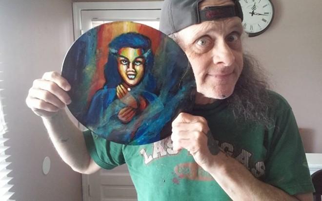 Wayne St. Wayne posing with some of his art.