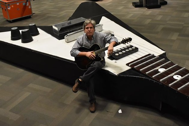 HP Newquist, executive director of the National Guitar Museum, sits atop the world's largest guitar. - DANIEL HILL