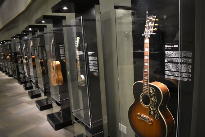 The walls of the exhibit are lined with guitars from throughout history. - DANIEL HILL