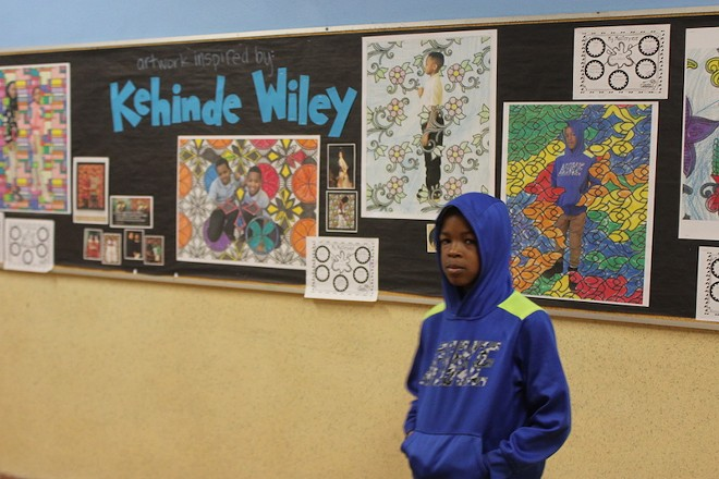 Jaran May poses in front of his artwork, now hanging on the walls of Bryan Hill Elementary School. - SARAH FENSKE
