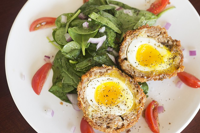 The Scotch egg features a soft-boiled egg wrapped in sausage and coated in breadcrumbs. - MABEL SUEN