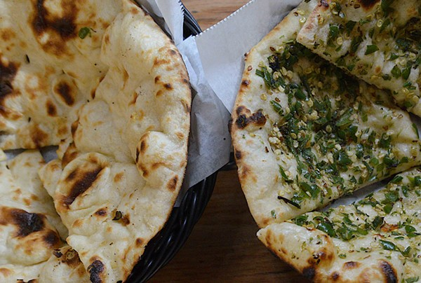 Naan dough is placed in a tandoor oven, giving it a distinct flavor. - TOM HELLAUER