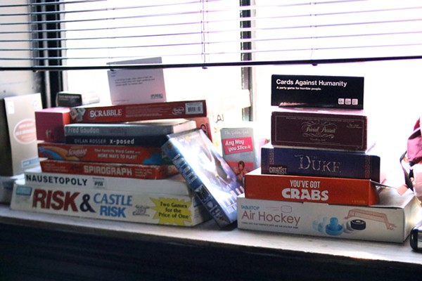 Board games are stacked by a window. - CHELSEA NEULING