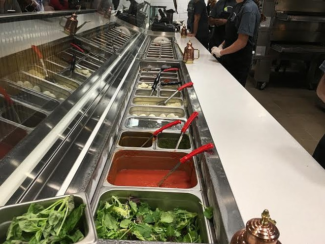 Pizza chefs prepare customized orders for hungry patrons. - CHERYL BAEHR