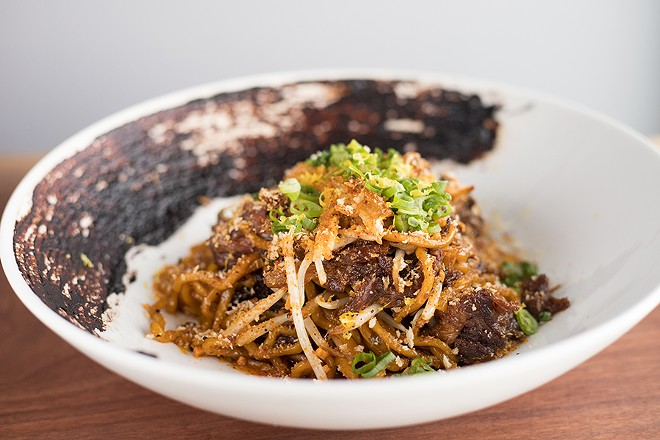Braised short-rib garlic noodles include black garlic, roasted chiles and togarashi gremolata. - MABEL SUEN