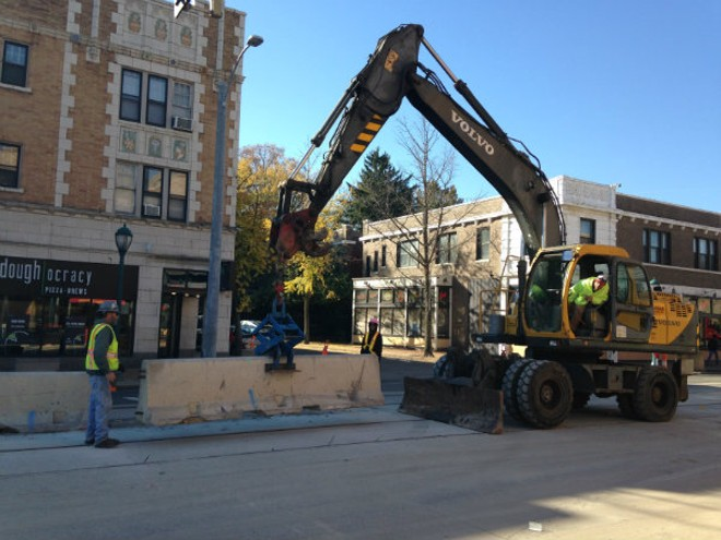 Workers on Tuesday remove concrete barrier in the Delmar Loop. - DOYLE MURPHY/RIVERFRONT TIMES