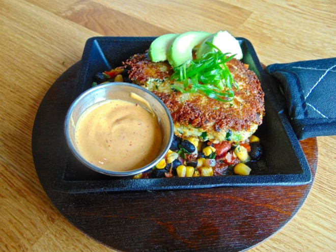 The wood-fired crab is made with jumbo lump crab and is served over a black bean, corn and tomato salsa. Chipotle mayo is served on the side. - EMILY HIGGINBOTHAM