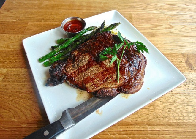 The Delmonico ribeye is aged for 28 days before it hits the grill. - EMILY HIGGINBOTHAM
