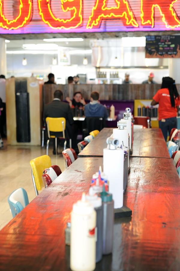 Colorful chairs flank long wooden tables. - PHOTO BY KELLY GLUECK
