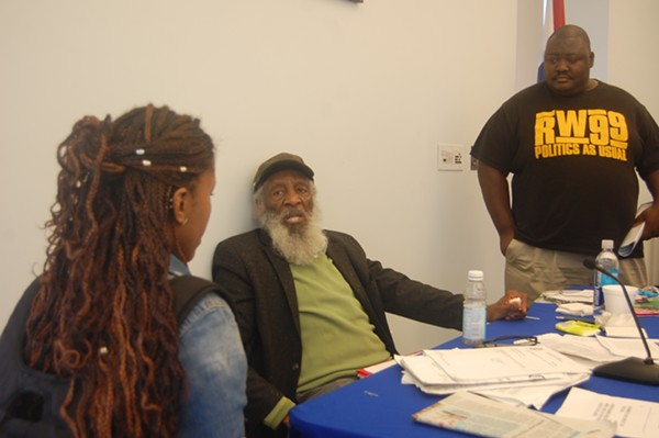 Scholars Brittany R. Mosley and Jeremy Shaw gathered around Dick Gregory to have autographs signed and ask questions. - PHOTO BY HARLAN MCCARTHY