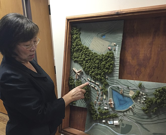 Minji Stark shows off a plan for Peace Village. - PHOTO BY ERIC BERGER