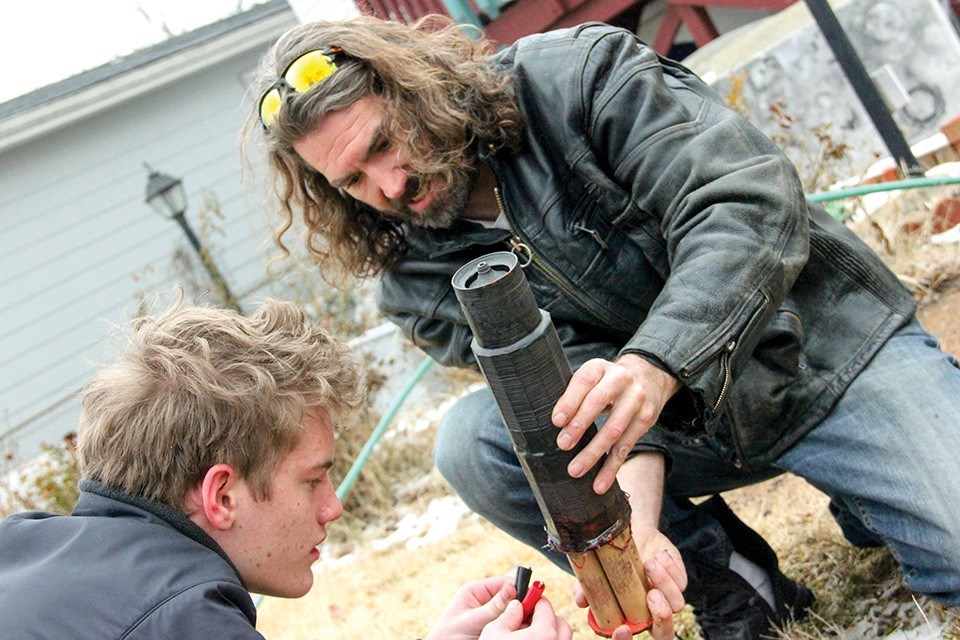 Brian Stofiel and an intern inspect the detritus of a backyard engine test. - DANNY WICENTOWSKI