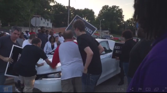 Protester Phillip Weeks (at left with sign) backpedals away from a Chrysler driving through a demonstration in Ferguson. - IMAGE VIA USTREAM