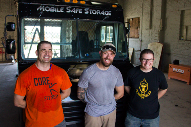 Justin Hulsey, center, has an armored van and a team of veterans to protect it. What he doesn't have is a vending license. - PHOTO BY DANNY WICENTOWSKI