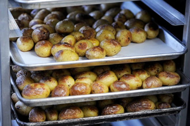 Yolklore's roasted potatoes are smashed on the grill and sprinkled with sea salt and herbs. - HOLLY RAVAZZOLO
