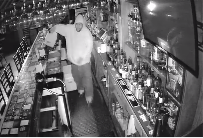 An arsonist pours flammable liquid inside Ole North Town Bar & Grill. - IMAGE VIA SLMPD