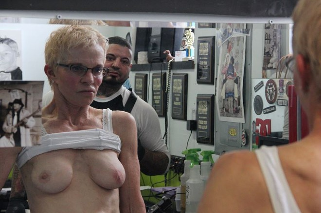 Catalano hovers while Kilhoffer inspects the newly implanted diamond stud in her right breast.