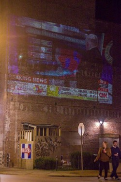 CNN was projected onto a brick building on Cherokee Street. - PHOTO BY DANNY WICENTOWSKI