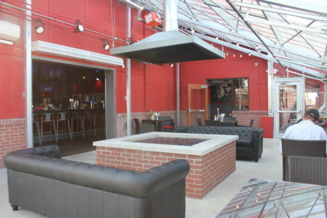 Outdoor seating includes leather couches and a  fireplace. - CHERYL BAEHR
