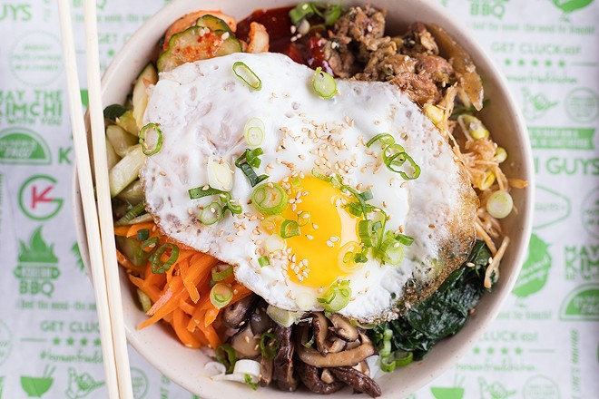 The bibimbap bowl is topped with green onions, sesame seeds, sesame oil and a fried egg. - MABEL SUEN