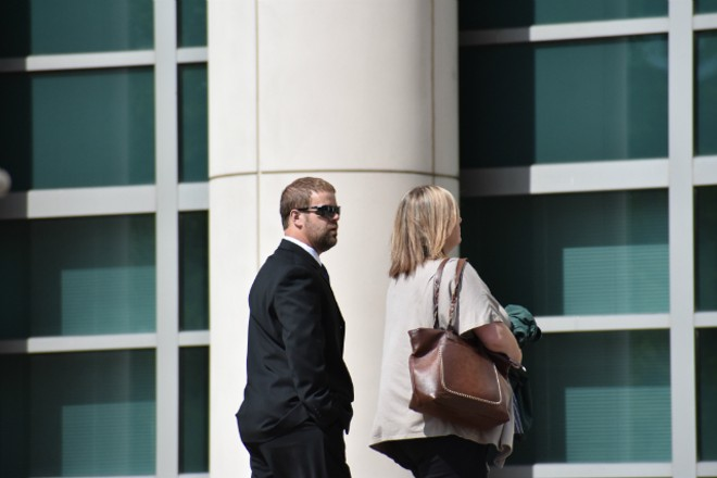 Ex-Mississippi County Sheriff Cory Hutcheson walks into federal court with his wife, Brittney. - DOYLE MURPHY